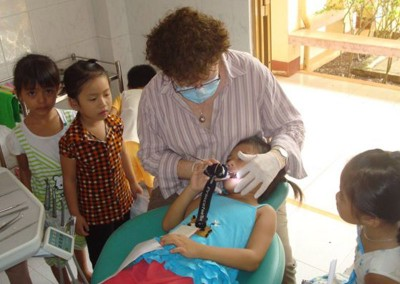 Lesley MacKrill (Hygienist) with patient holding headtorch as no power at the Long Tan Dental Clinic.