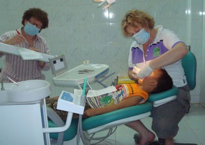 The original AVVRG chair with Lesley MacKrill (Hygienist) and Hellen Checker (Hygienist) working on a young Vietnamese patient at the Long Tan Dental Clinic.